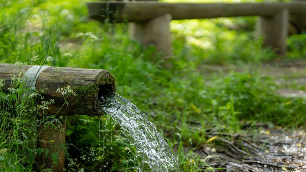 water flowing through bamboo tube during daytime
